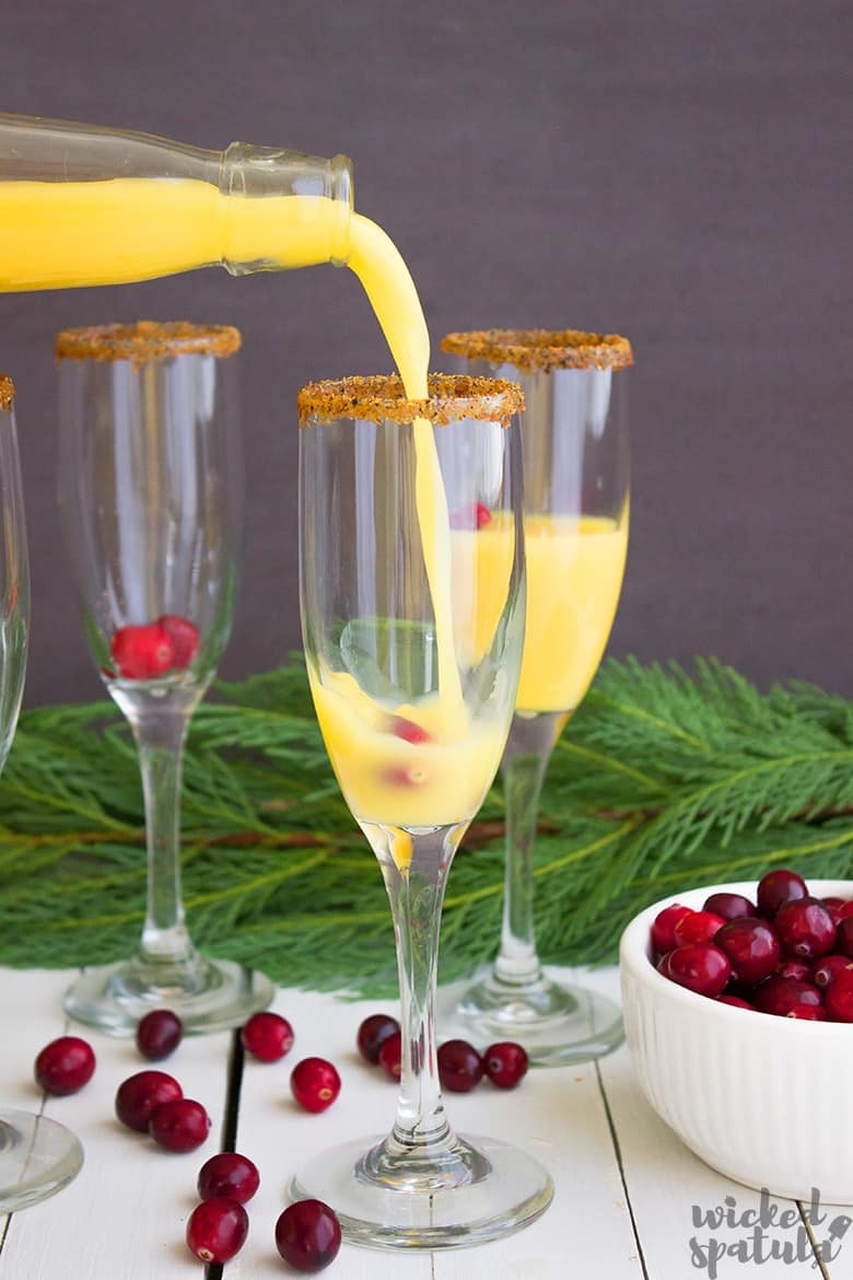 orange juice being poured into champagne glass