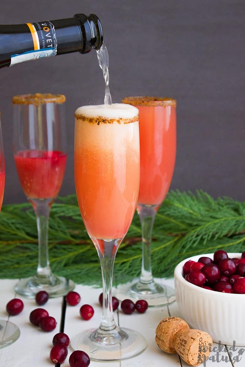 pouring prosecco into mimosa with cranberry juice