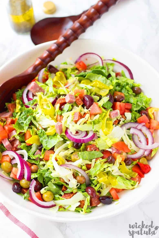 Italian green salad in bowl with spoon