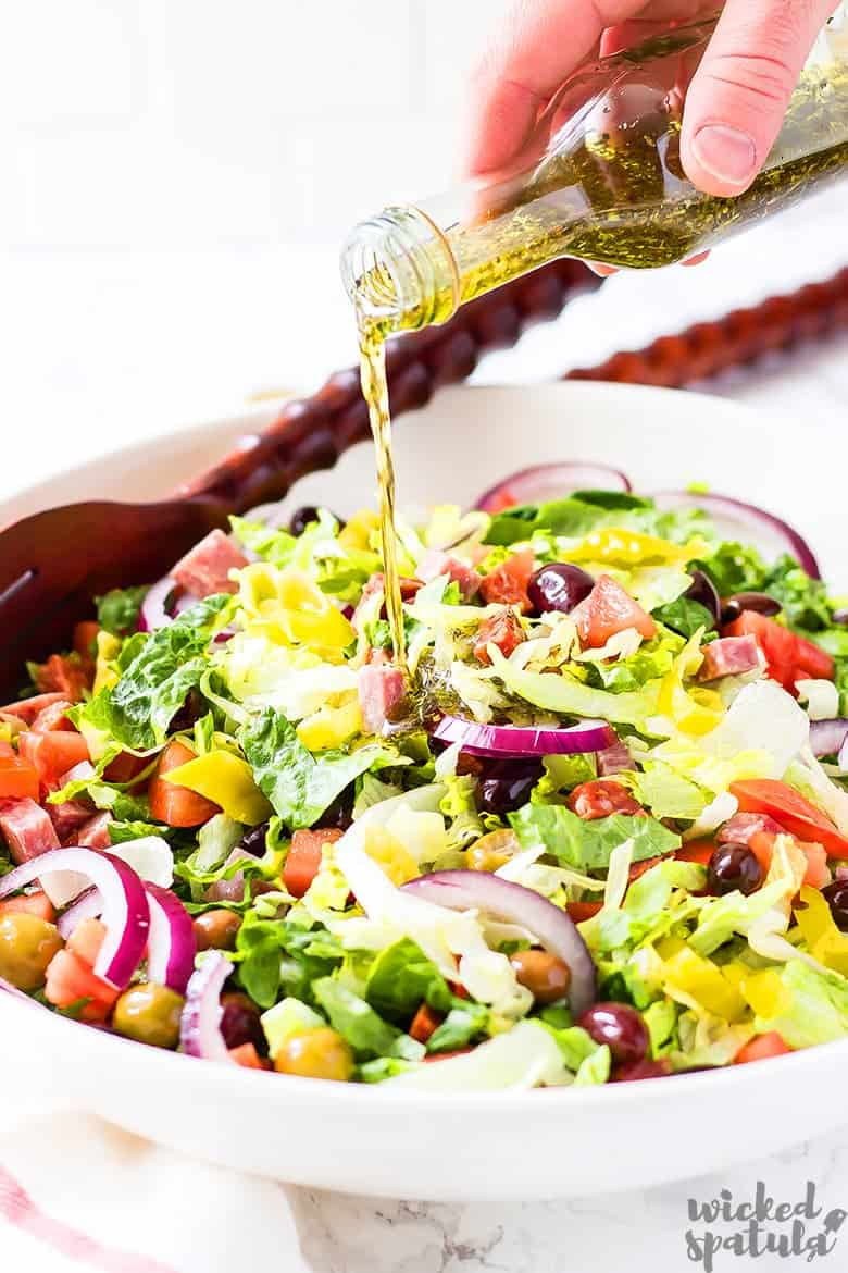 Italian salad with dressing being drizzled
