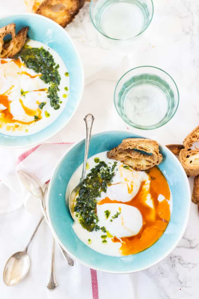 Turkish Poached Eggs - Garlic infused yogurt gets topped with poached eggs, spiced browned butter, and a fragrant chimichurri