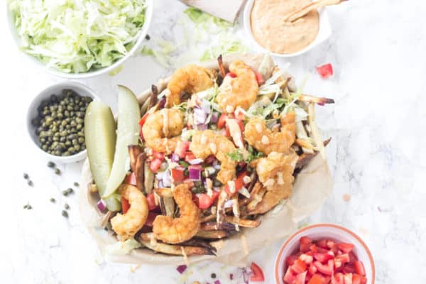 Shrimp Po'Boy FRIES!! These oven baked fries are topped with crispy fried shrimp, shredded lettuce, tomato, onion, capers, pickles, and a totally tasty remoulade sauce. Seriously, heaven on a plate! Gluten free and Paleo friendly!