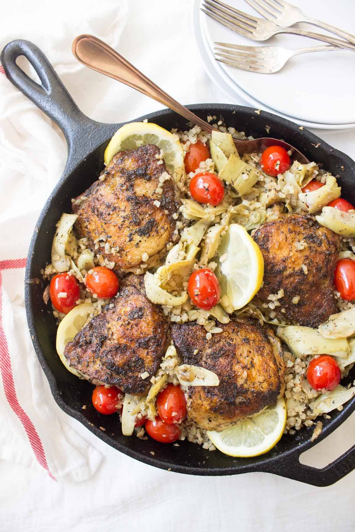 This Greek Lemon Chicken is bursting with flavors from a delicious marinade, cherry tomatoes, artichokes, and a lemon cauliflower rice all made in one pan!