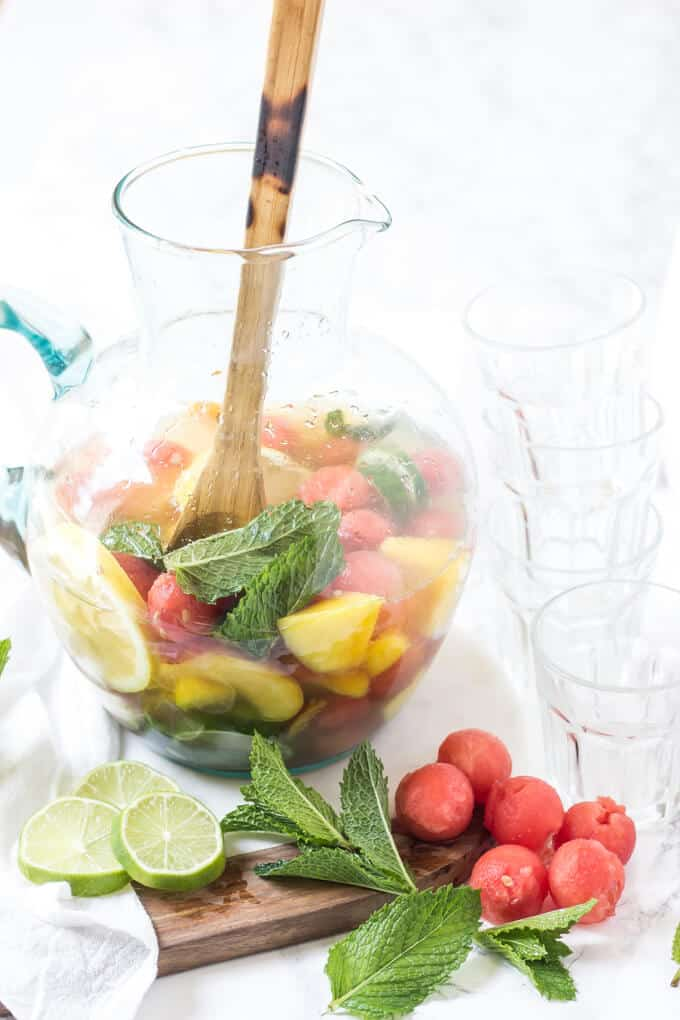 peach sangria in a pitcher with limes, mint and watermelon garnish