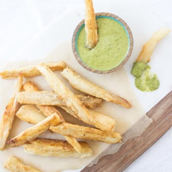 Yuca Fries on board served with green sauce in a bowl