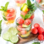 summer white sangria in glasses with melon balls and mint garnish