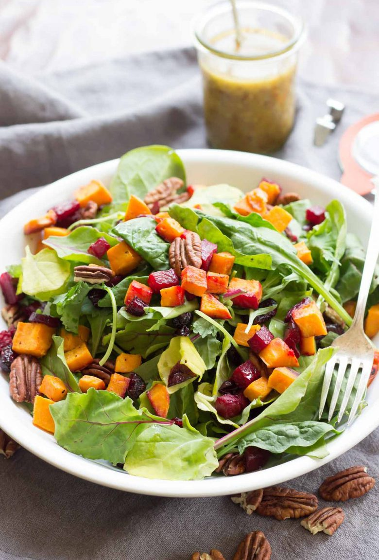 This Roasted Harvest Salad is packed full of sweet potatoes, beets, cranberries, and pecans! It gets topped with a delicious maple mustard dressing!