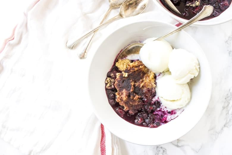 This Slow Cooker Mixed Berry Paleo Cobbler has that classic syrupy fruit all topped with a fluffy pastry that gets all mixed up in one bowl.