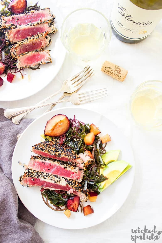 ahi tuna salad on a plate with wine