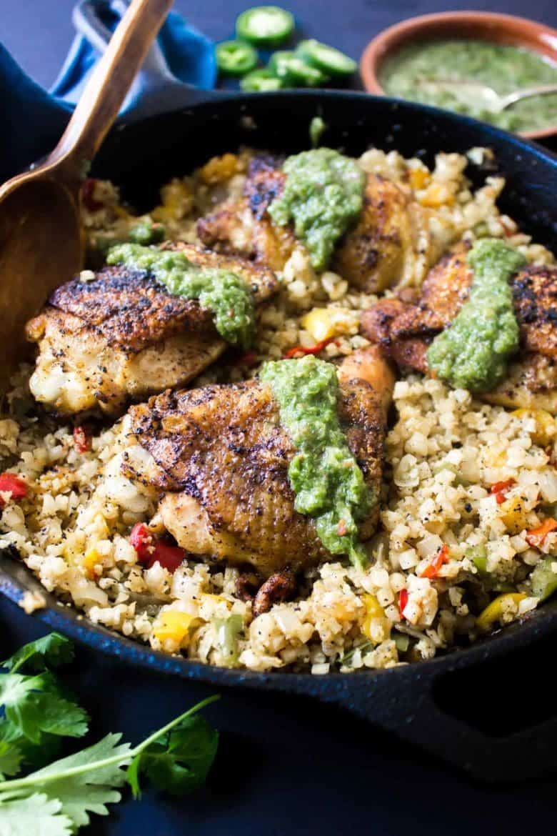 This flavorful Latin Paleo Arroz Con Pollo is packed full of delicious cauliflower rice, crispy chicken, onions, peppers, and a tangy hot sauce!