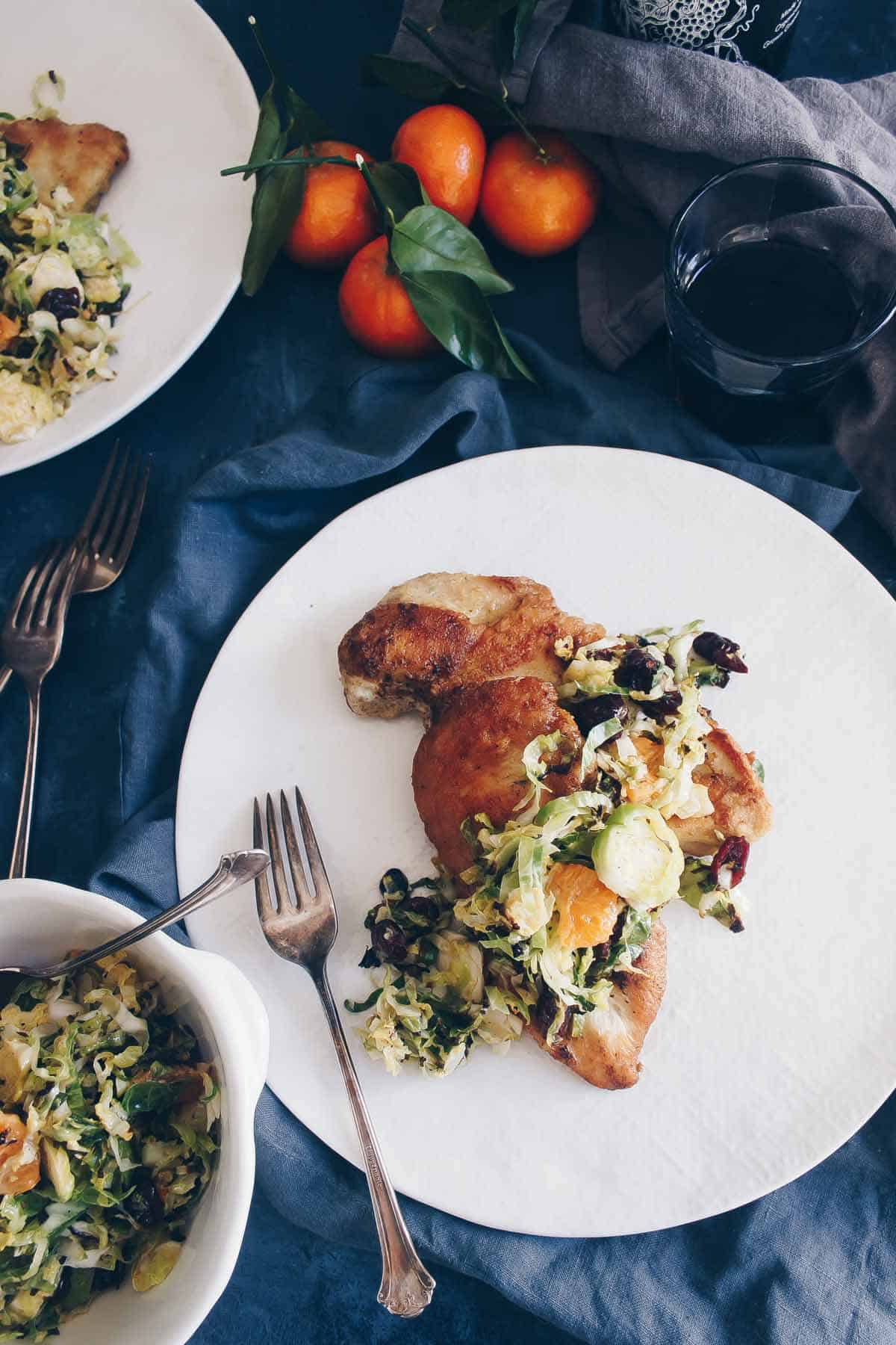 This quick 30 minute meal is just as elegant as it is nutritious. Pan seared chicken gets topped with Brussels sprouts slaw with oranges and cranberries. Paleo friendly!