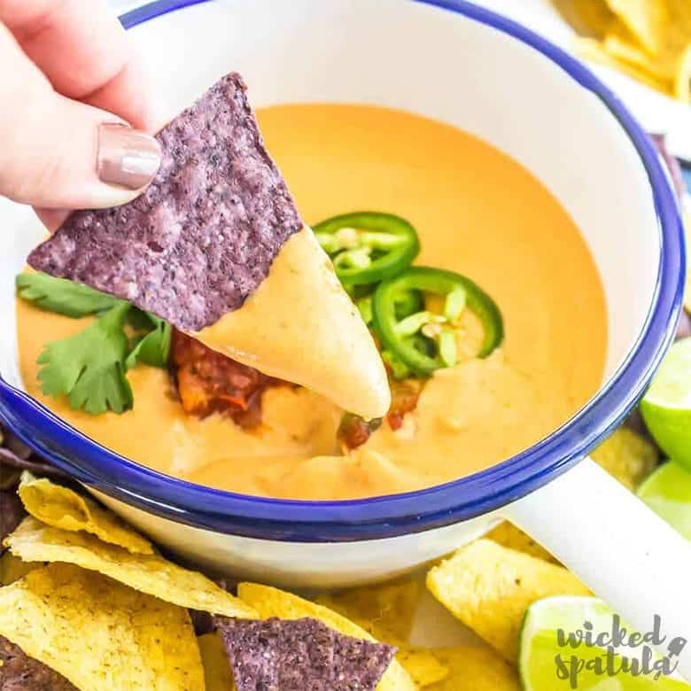 The Best Vegan Queso Recipe - Bowl with queso and dip on chip