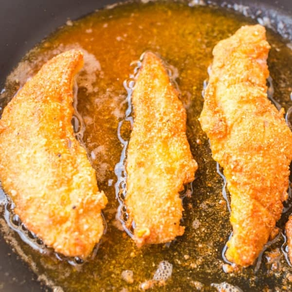 paleo chicken tenders frying in coconut oil