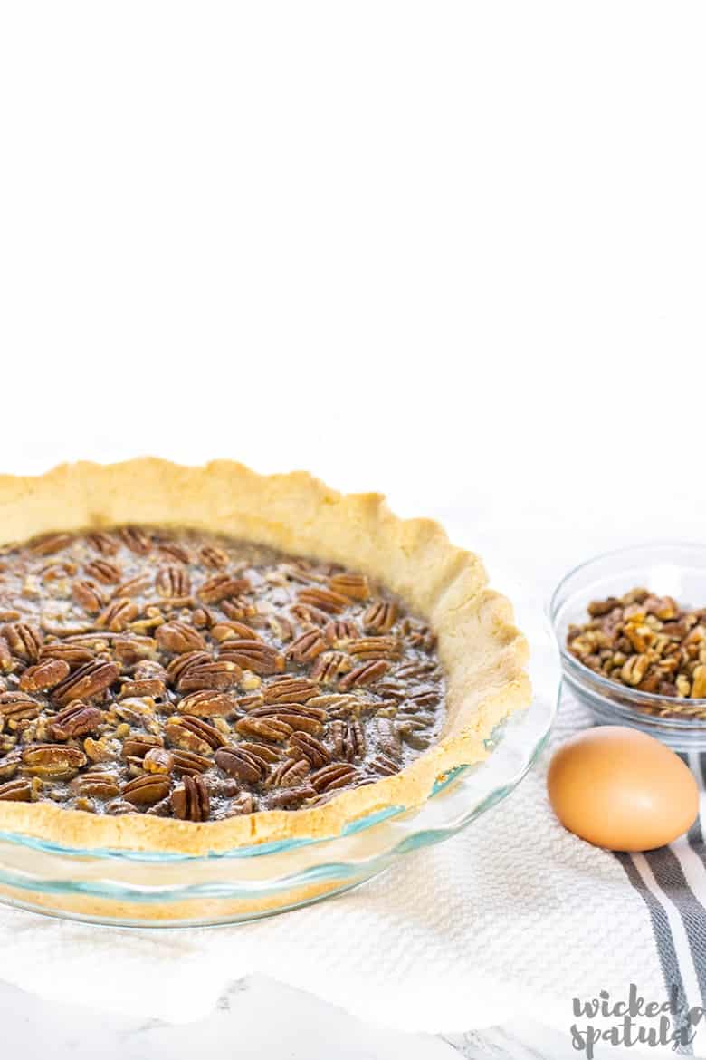 pie with an egg and bowl of pecans