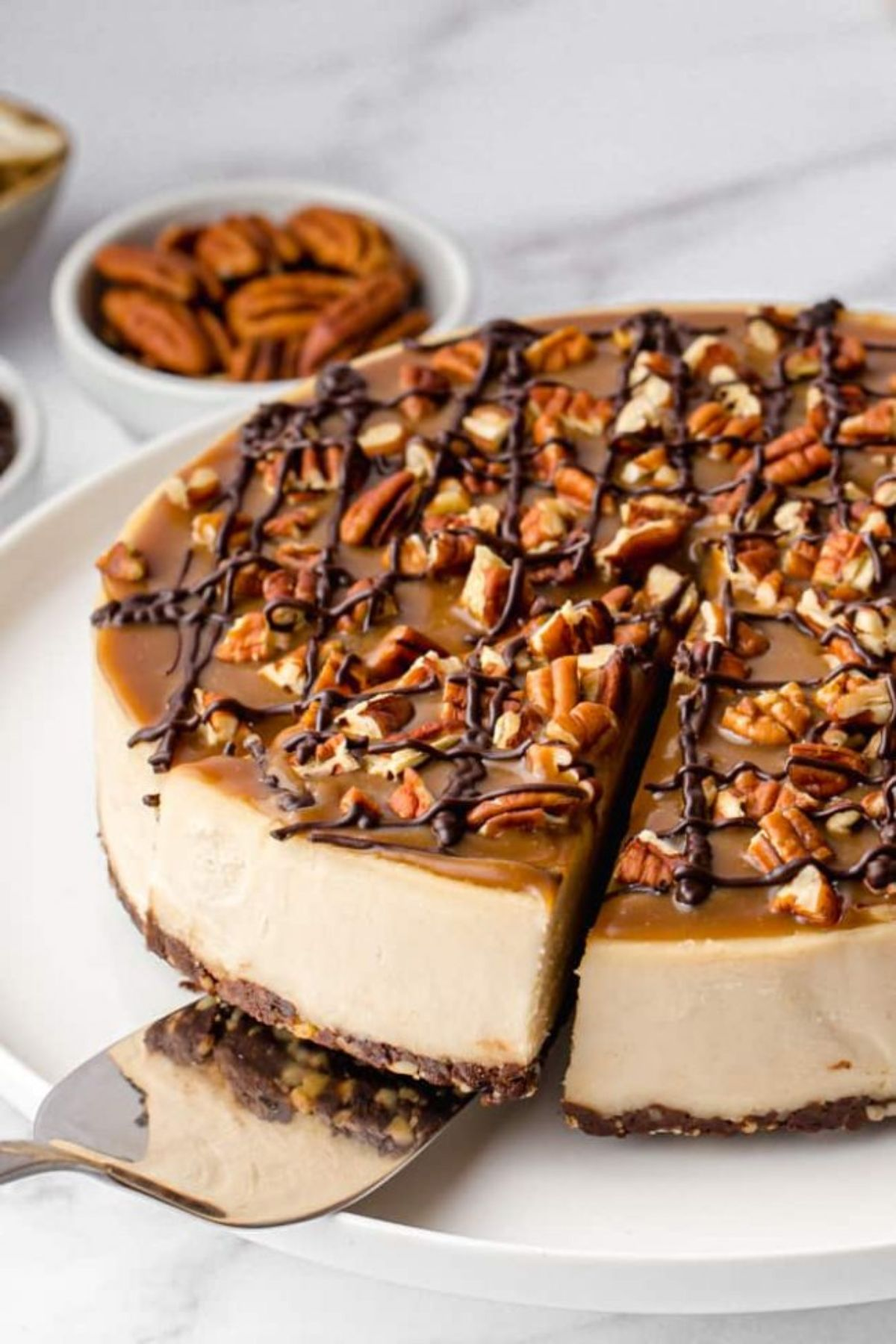 A plate of caramel coloured cheesecake with one segment cut out and being liften out by a cake slice. A bow of ppecans is in the back