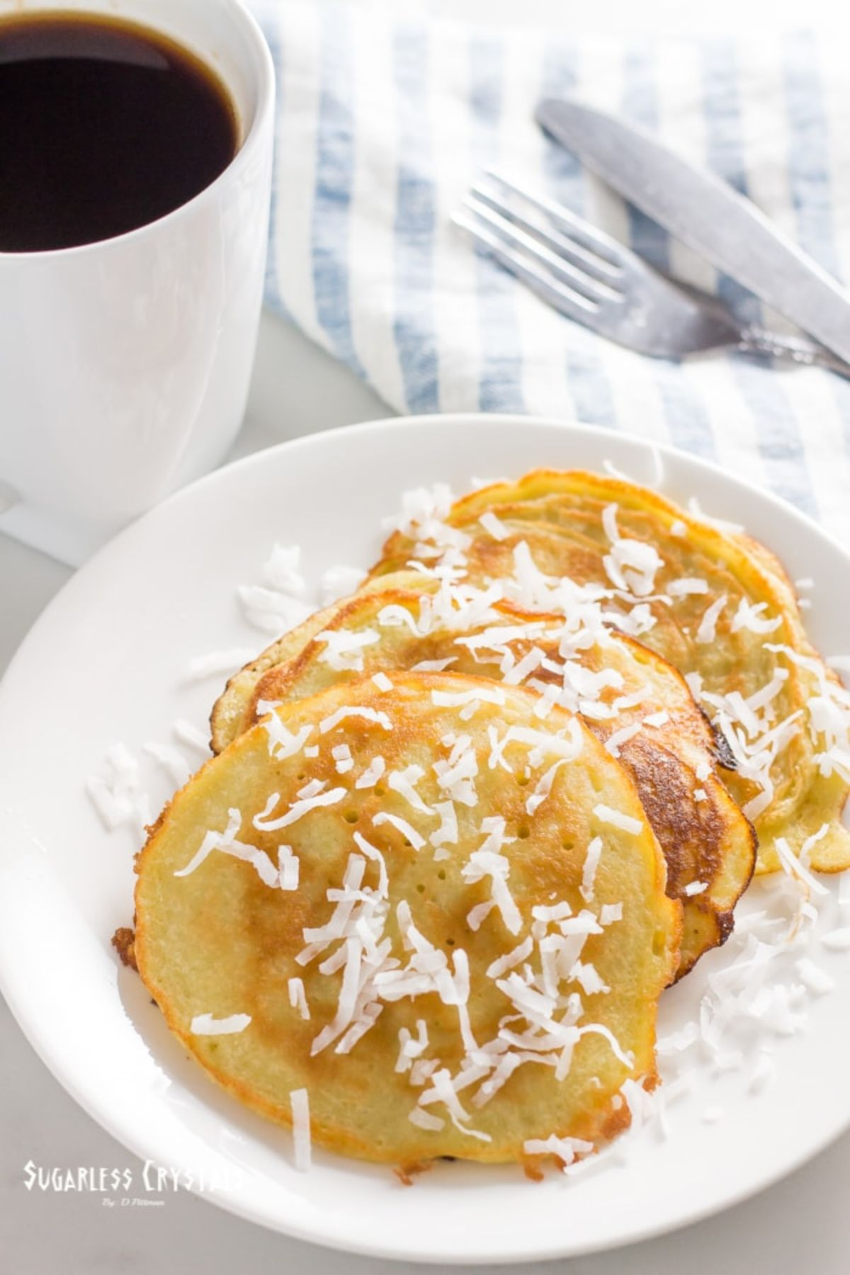 A white palte with pancakes on it, sprinkled with shreded coconut. A cup of coffee and a knife and fork are behind it