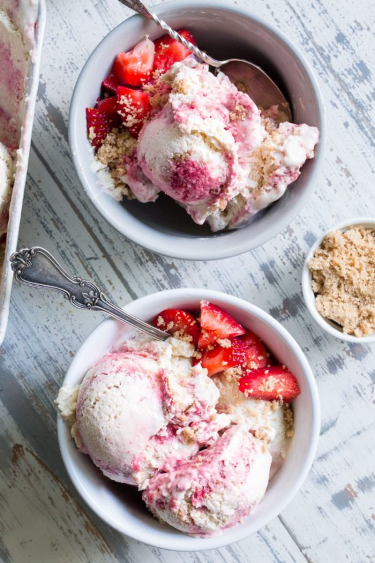 2 bowls of strawberry cheesecake ice cream with spoons sticking out of them, topped with fresh strawberries