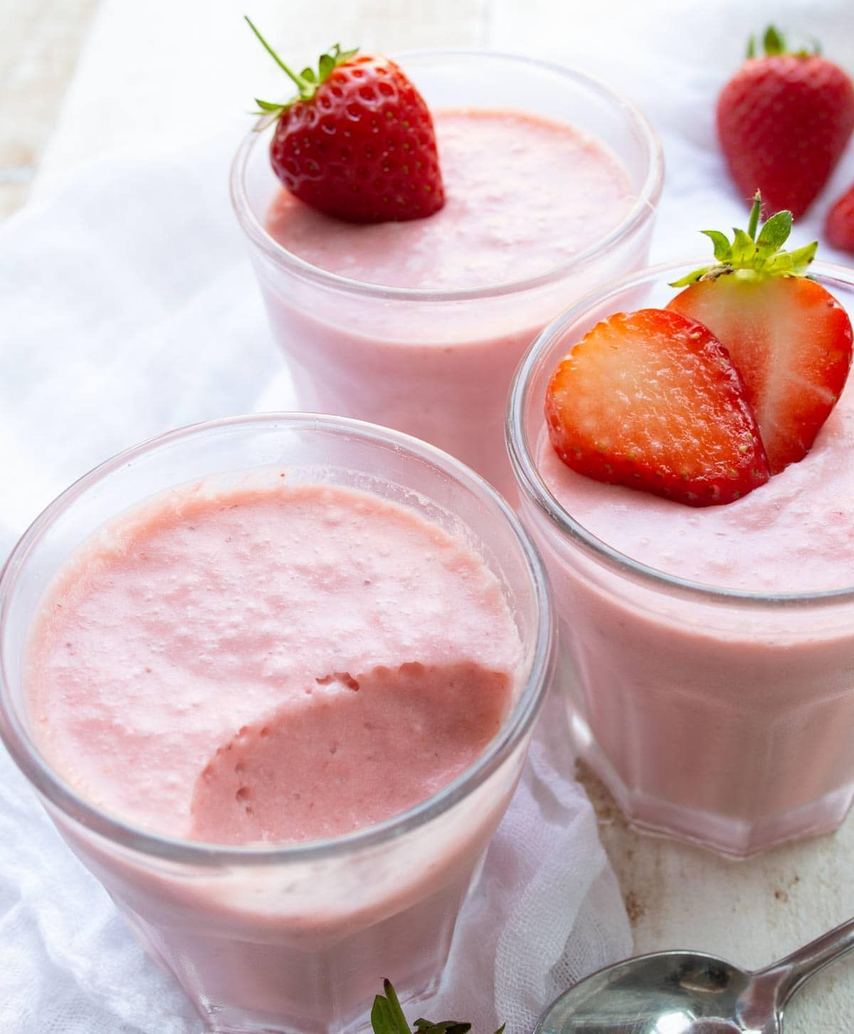 3 glasses of strawberry mousse topped with fresh strawberries