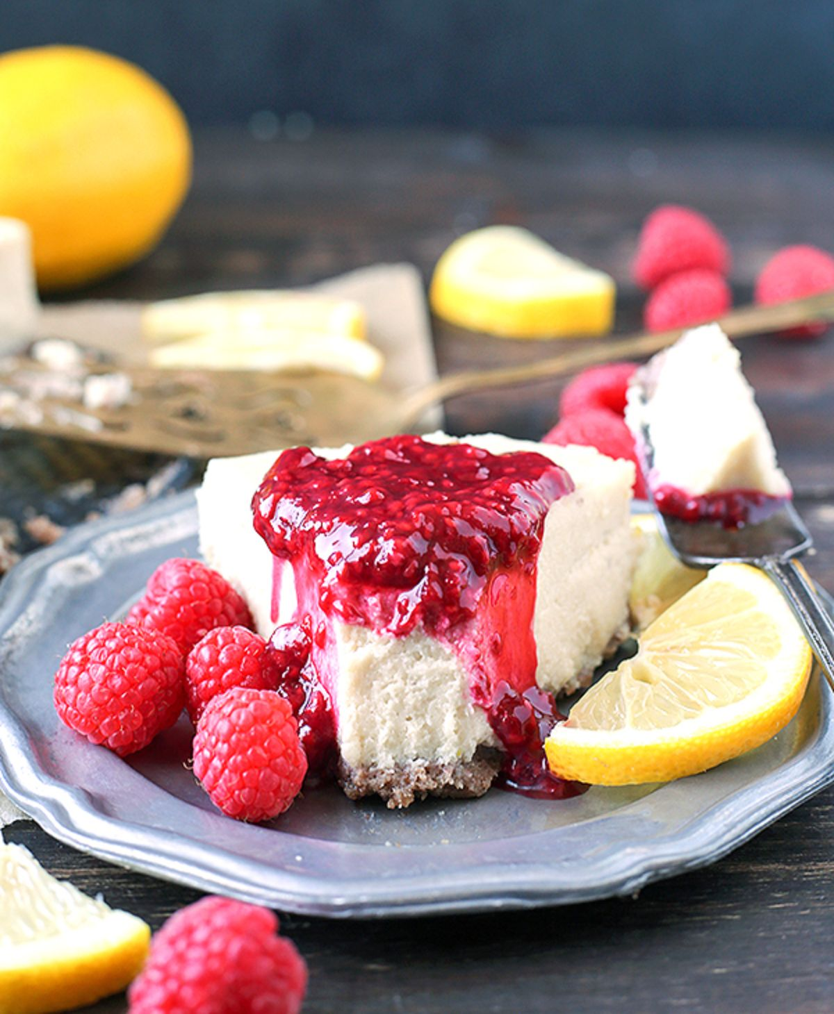 A blue plate with a segment of vanilla cheesecake drizzled with raspberry coulis and surrounded by lemon slices and fresh raspberries