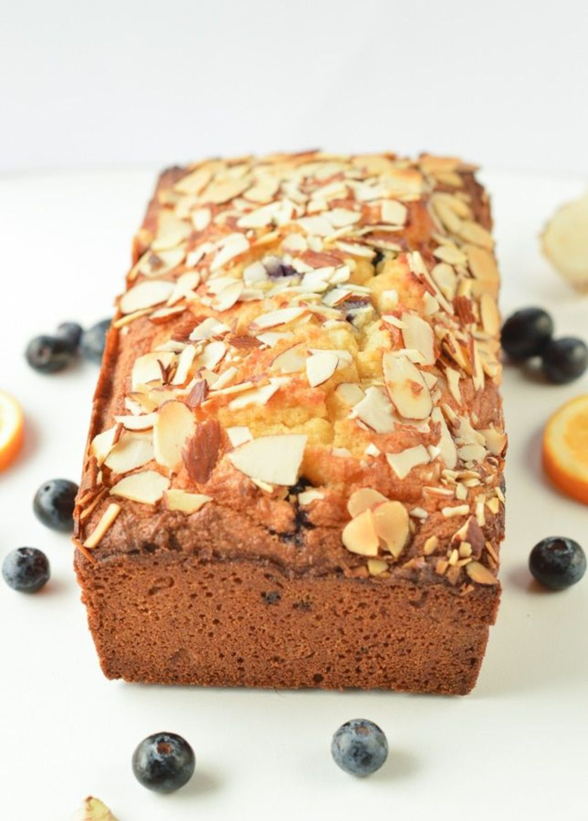 A loaf of blueberry bread topped with sliced almonds and blueberries scattered around it