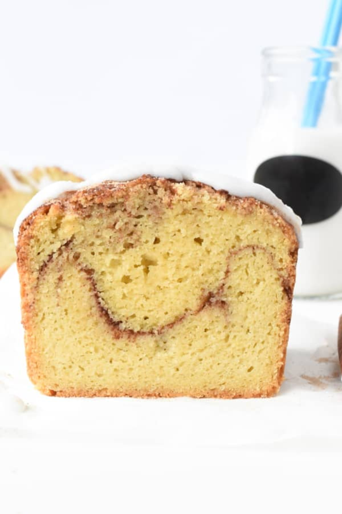 A cut away view of a loaf of cinnamon bread with white icing