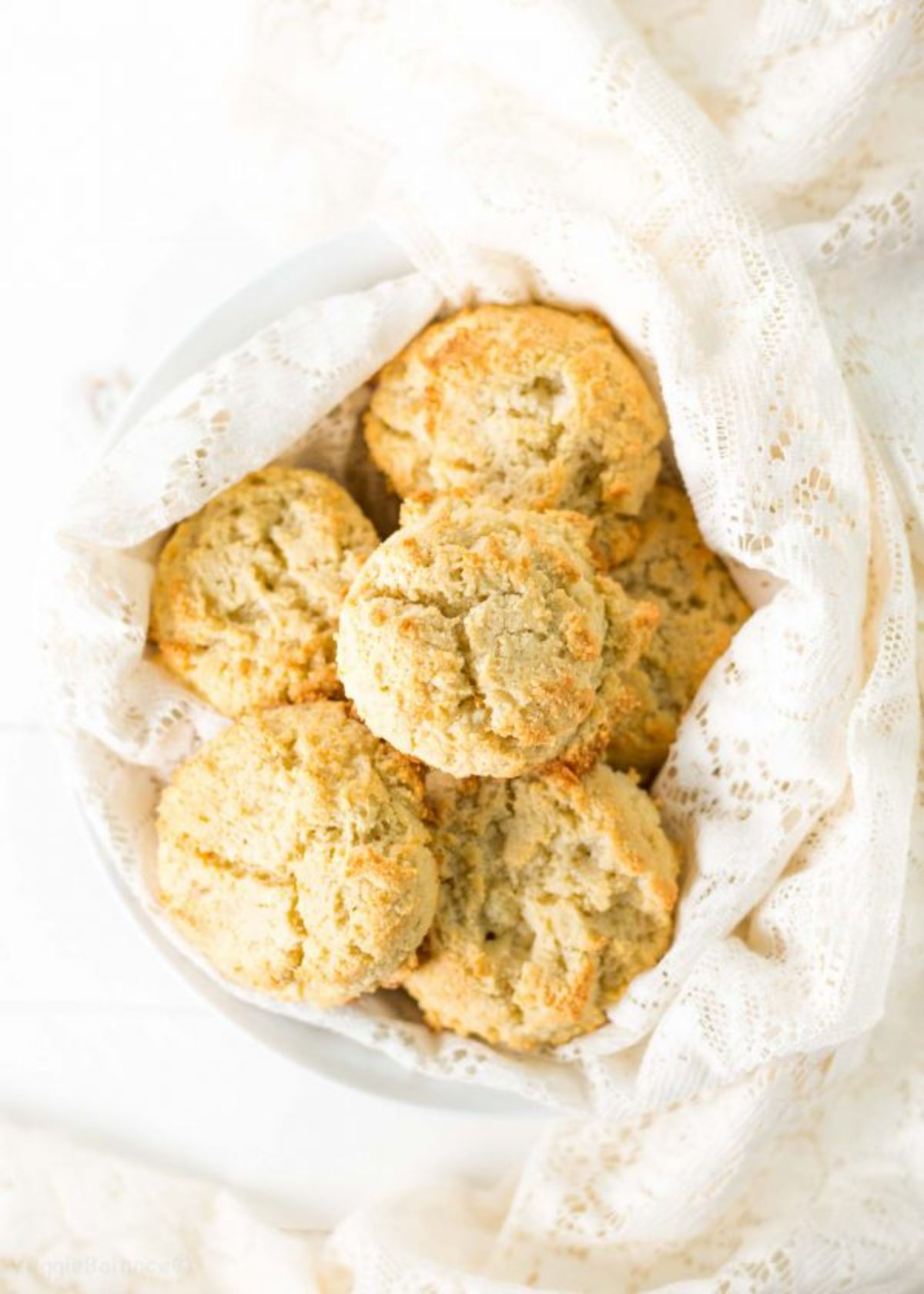 a cloth-covered basket containing a pile of biscuits
