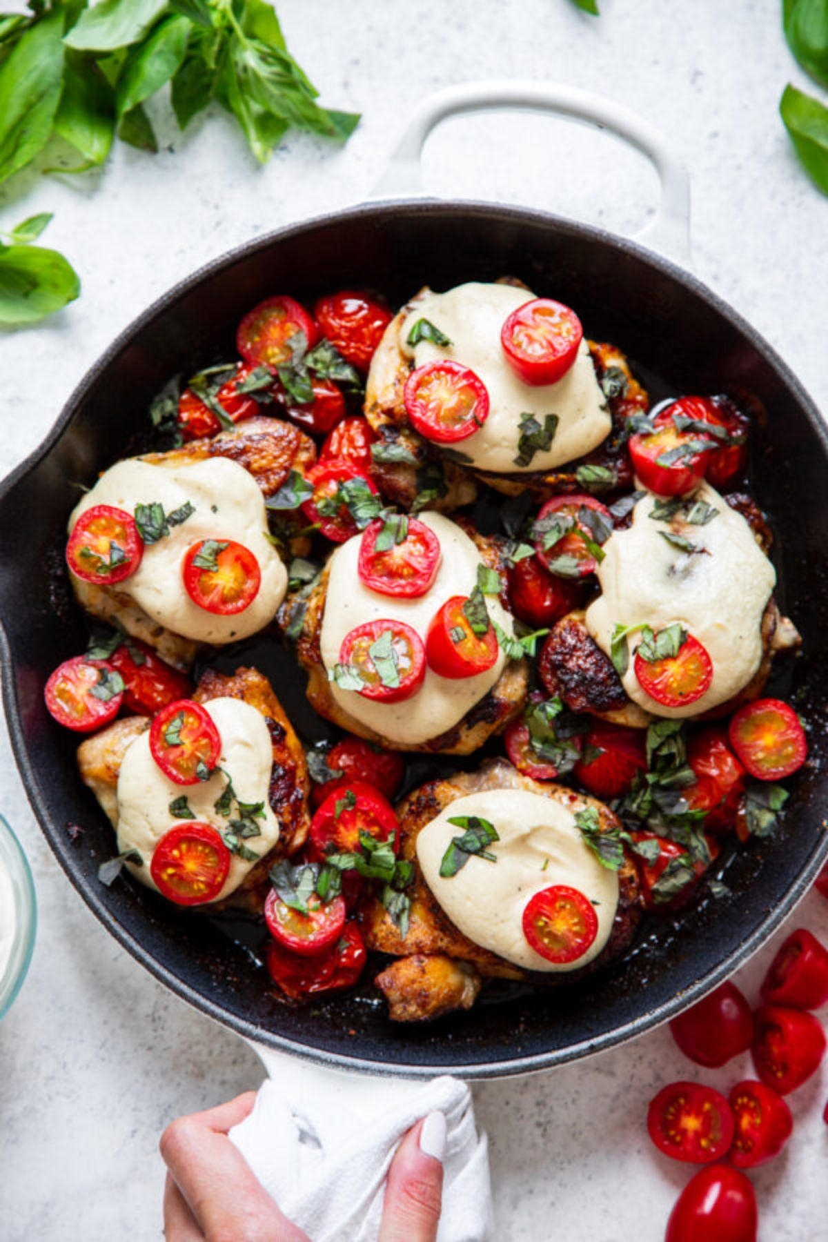 a skillet full of chicken thighs topped with cheese and tomatoes