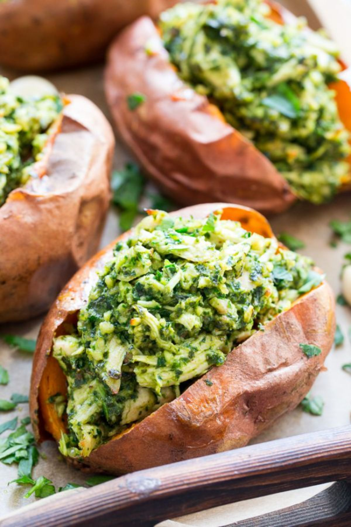 a baking tray with baked sweet potatoes stuffed with pesto chicken