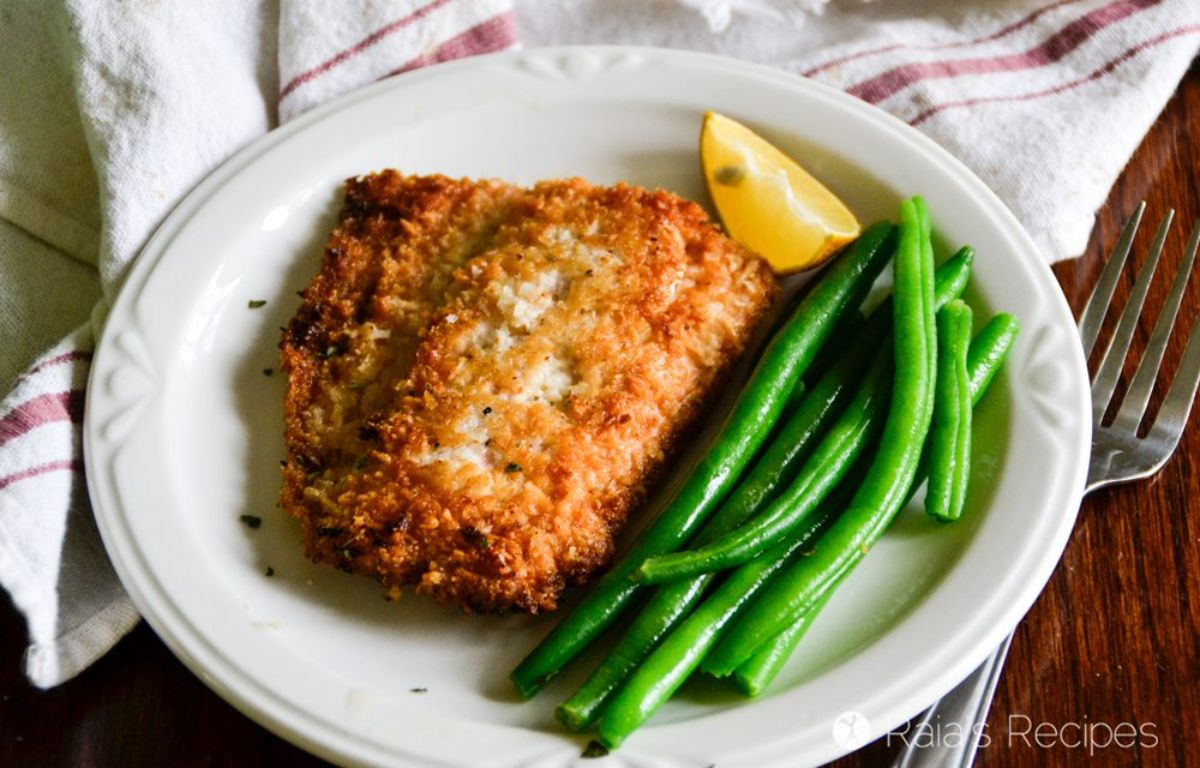 a white plate with a breaded fish fillet and green beans, garnished with a lemon edge