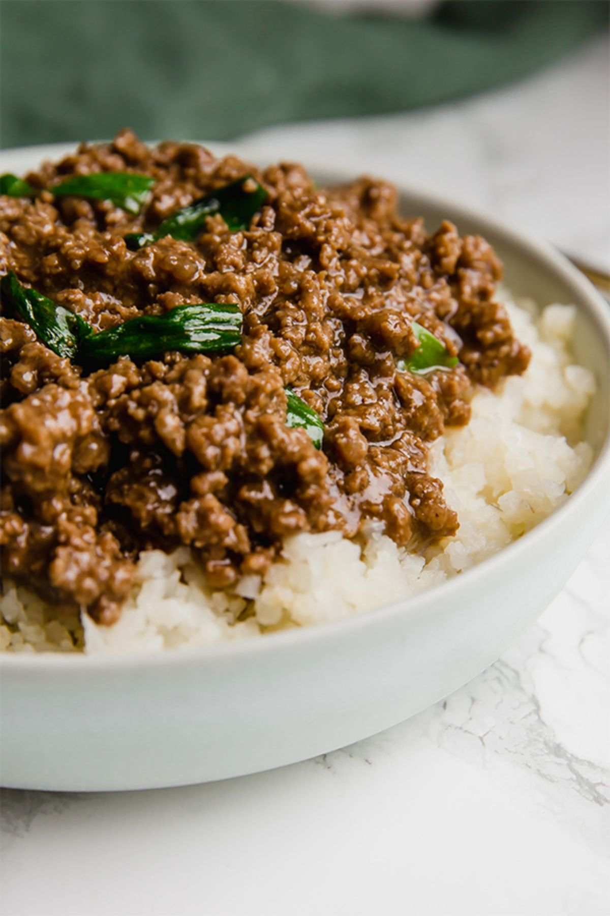 A white bowl of ground beef in sauce on top of rice