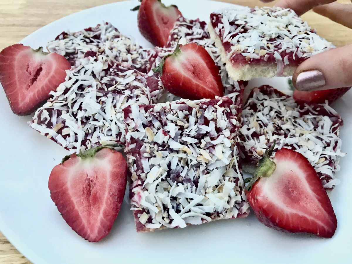 A plate of strawberry coconut bars surrouned by halved strawberries