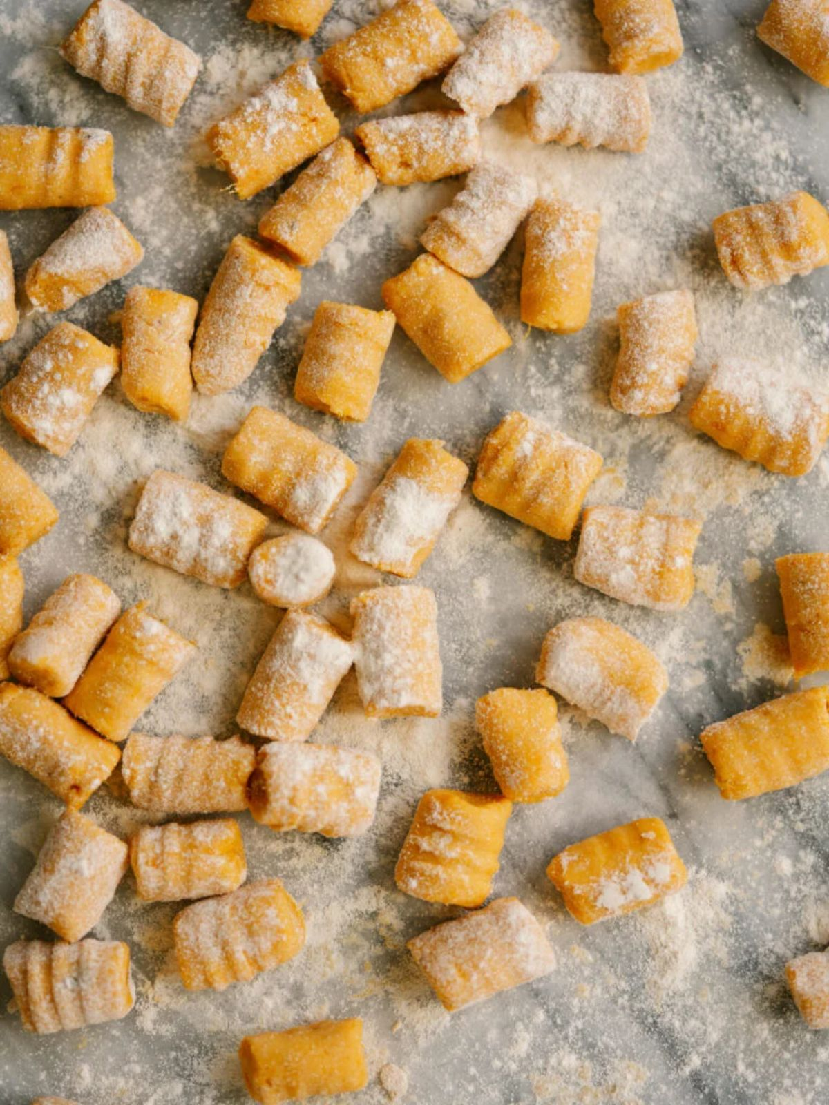 a baking tray with uncooked potato gnocchi, sprinkled with flour