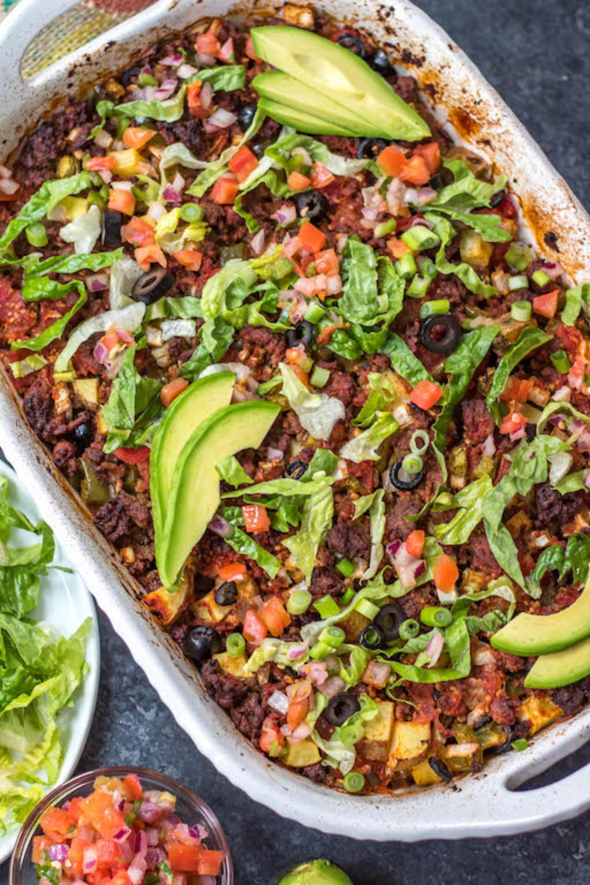 An oven dish full of beef casserole topped with avocado, lettuce, scalions and olives