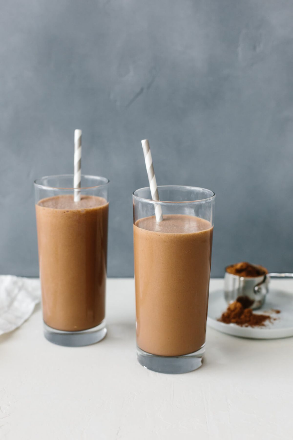 2 glasses of chocolate smoothie with straws sticking out