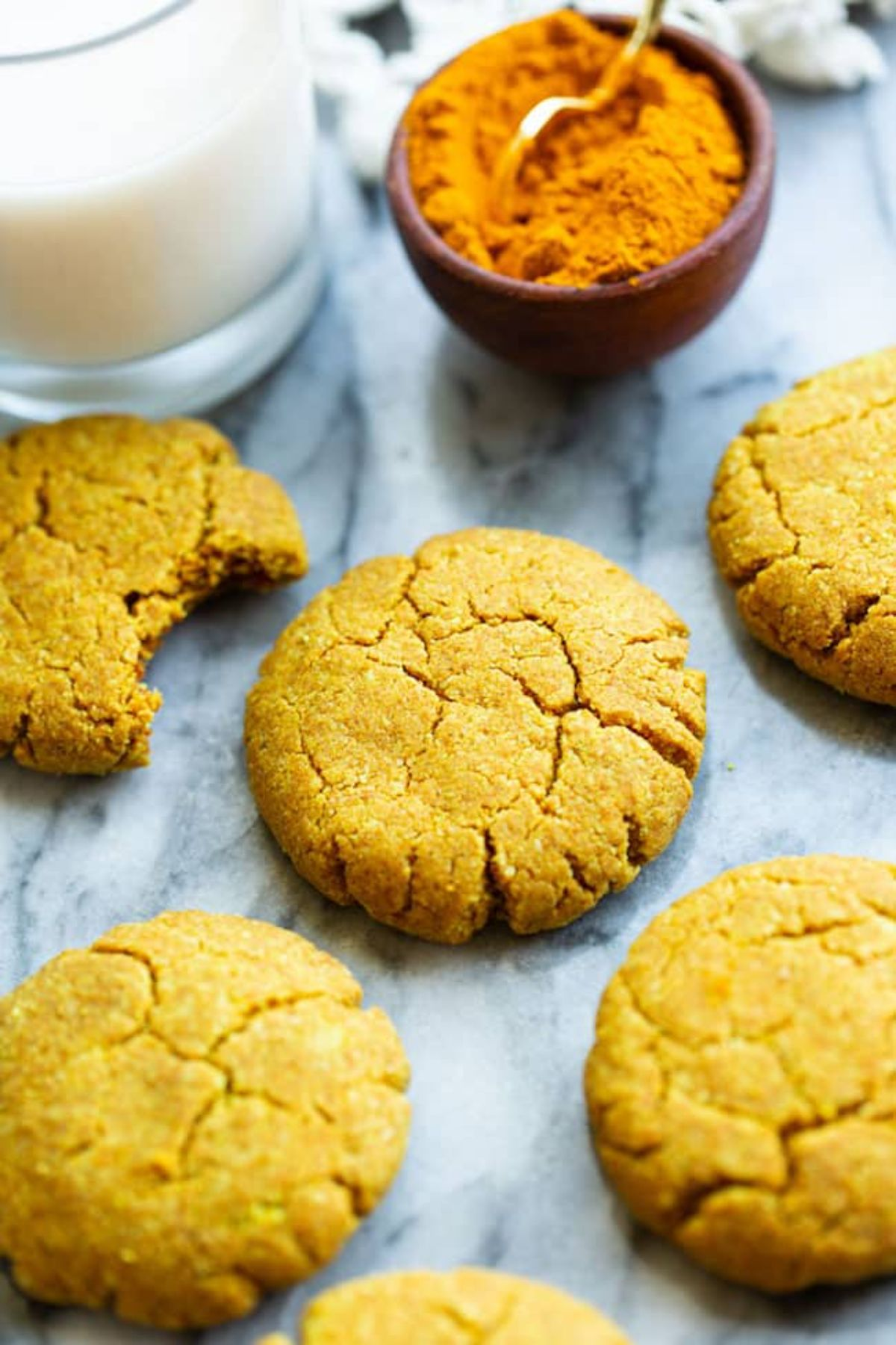 5 golden almond biscuits, one with a bit taken out of it. Behind is a glass of milk and a small pot of spice