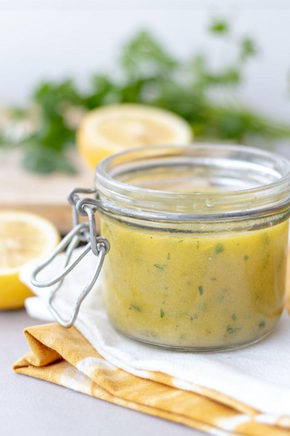 A kilner jar with clip full of lemon herb vinaigrette with lemons and hebrs just seen in the background