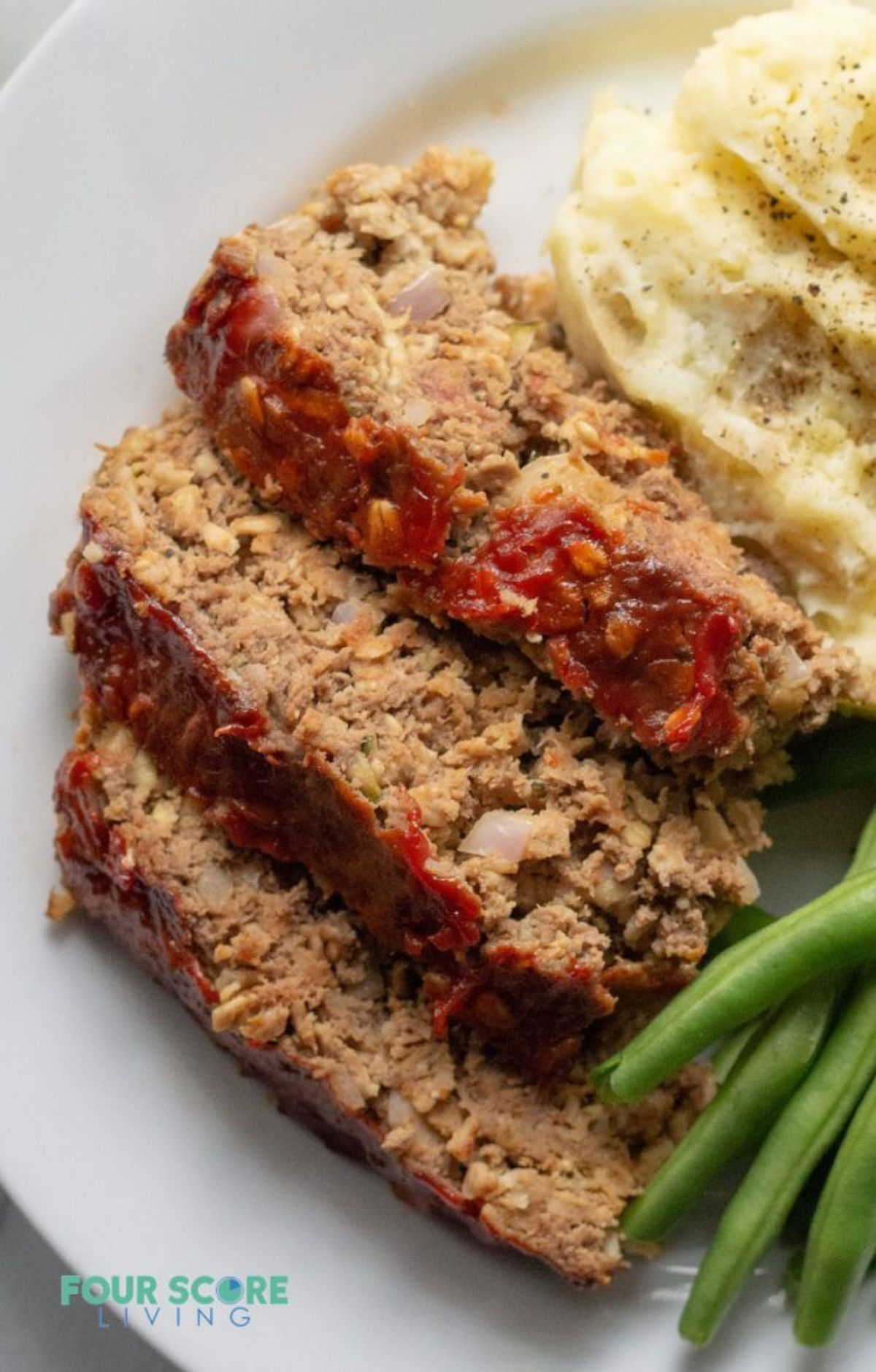 A white plate with slices of meatloaf, green beans and mash on it