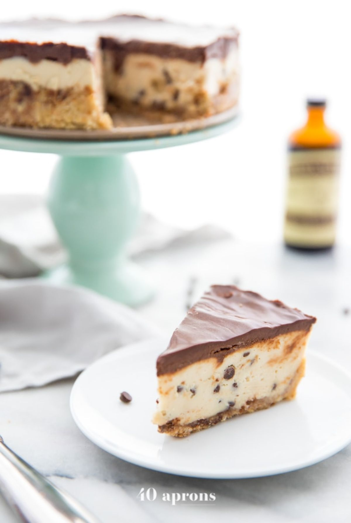 A cake stand with a layered cookie dough cheesecake with a slice cut out of it. A white palte with that slice is in front
