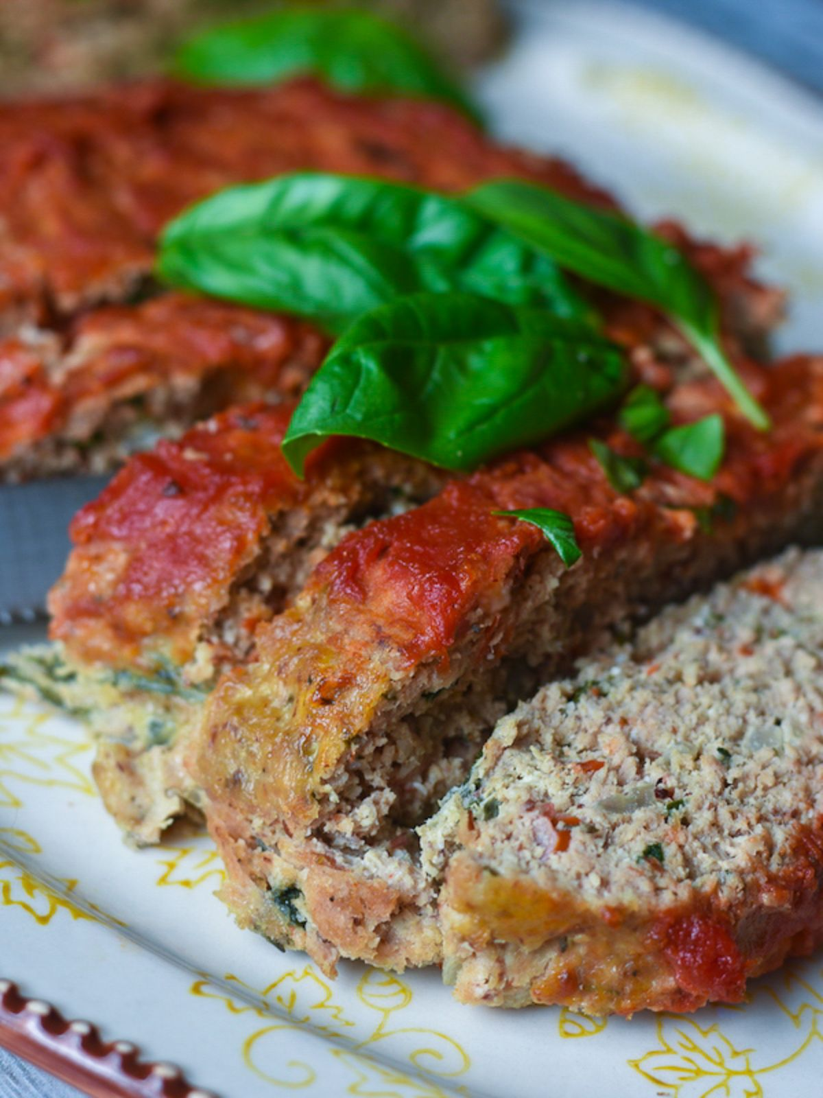 A partial shot of a platter with slices of meatloaf on it, topped with basil leaves
