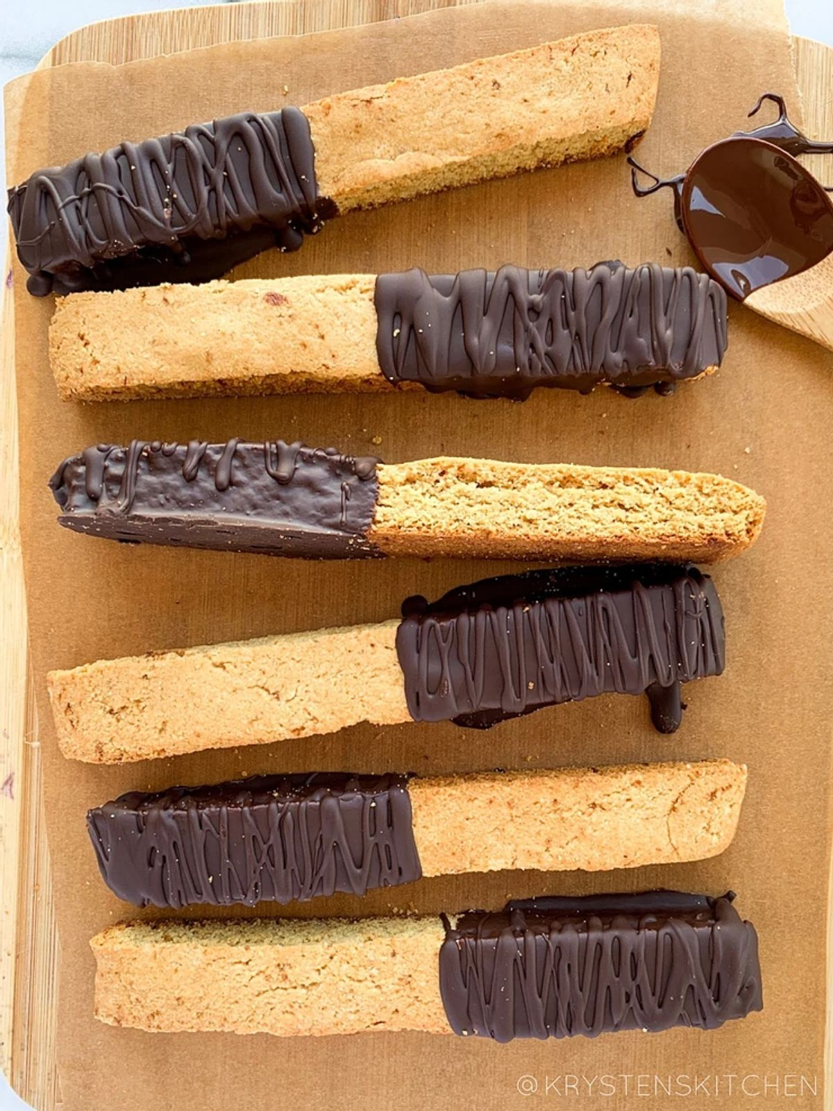 a wooden tray with 6 chocoloate-dipped almond biscotti