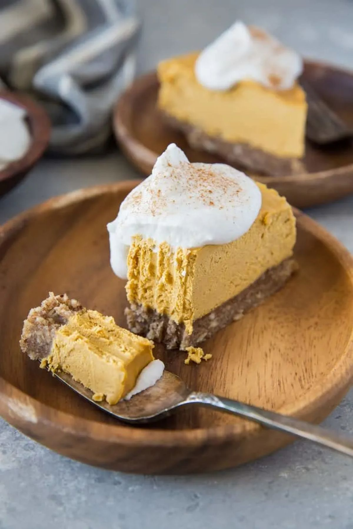 A wooden plate with a pumpkin cheesecake on it, topped with cream