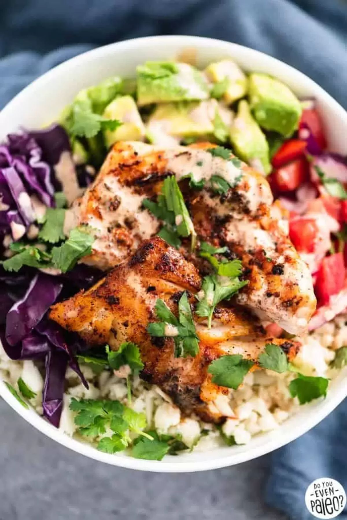 a bowl of fish, red cabbage, avocade, tomatoes and fish fillet, topped with chopped herbs