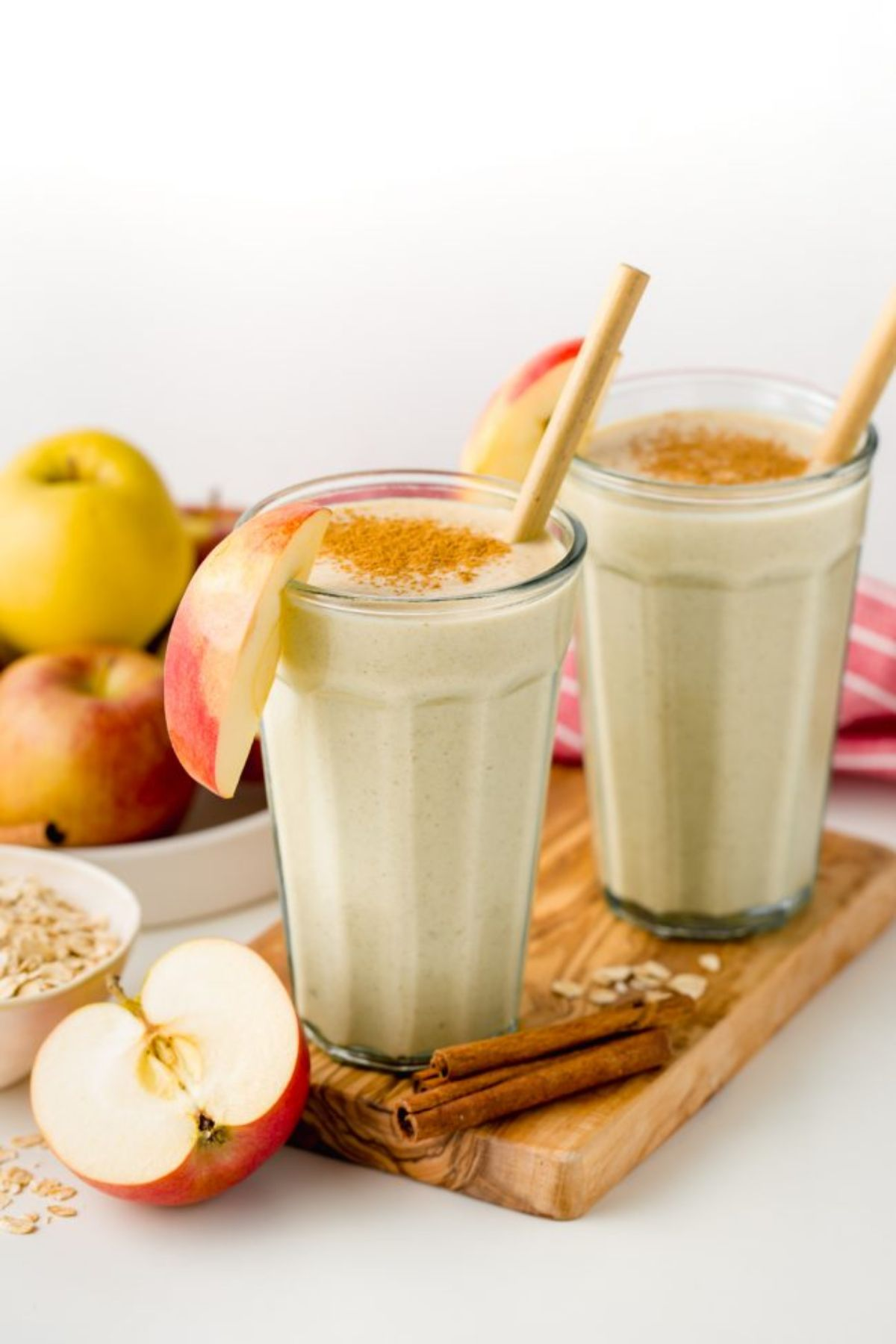 2 glasses of apple pie smoothie on a wooden board, garnished by apple slices, topped with cinnamon and surrounded by cinnamon sticks, apples and oats
