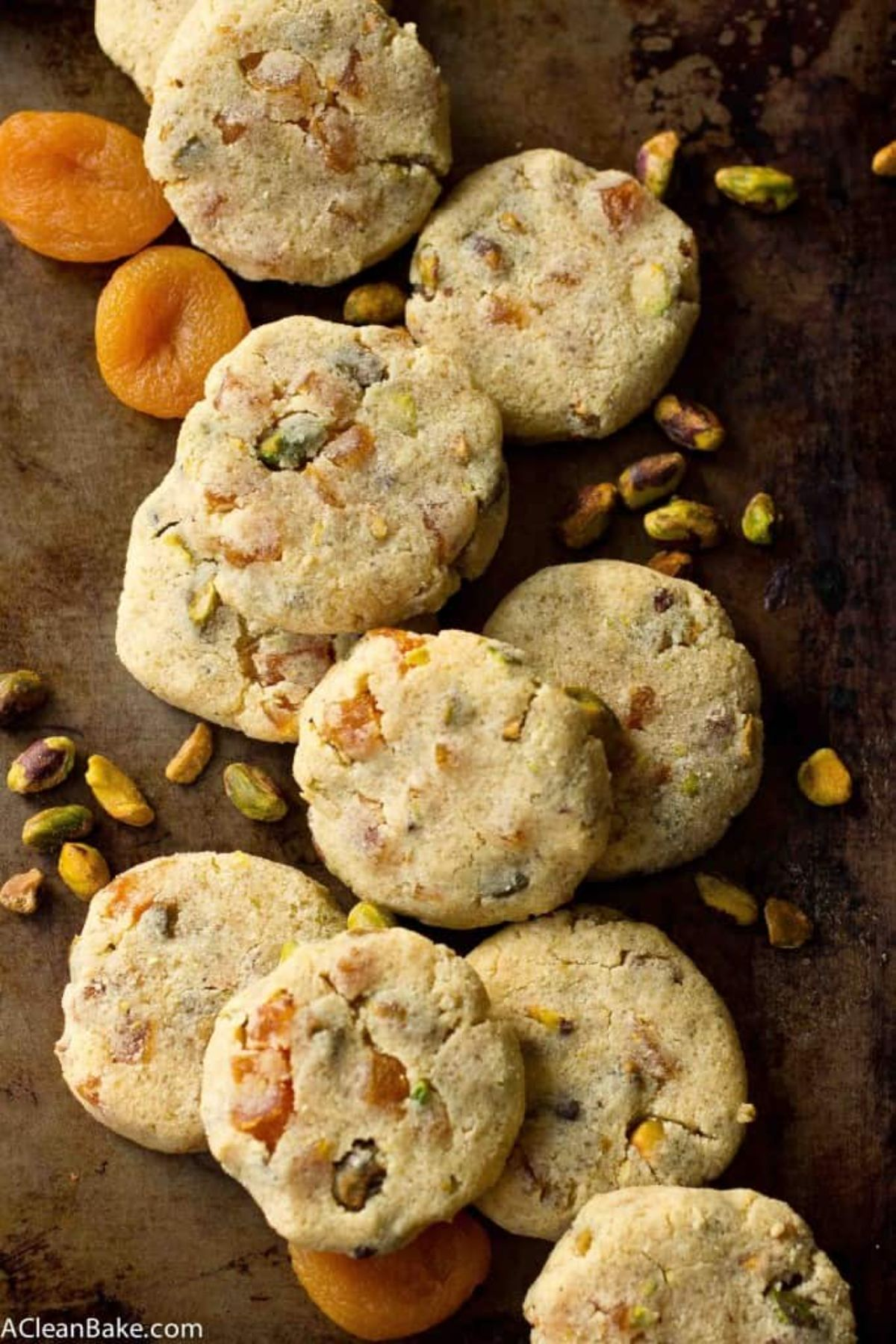 a pile of aprocot and pistachio biscuits with dried nuts and fruit scattered over them