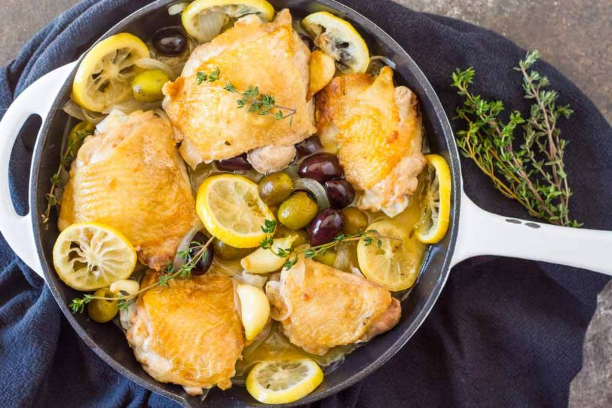 a skillet with chicken thighs, lemon slices and olives