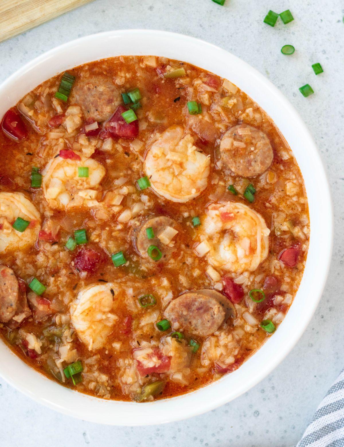 a white bowl of prawn and chorizo soup