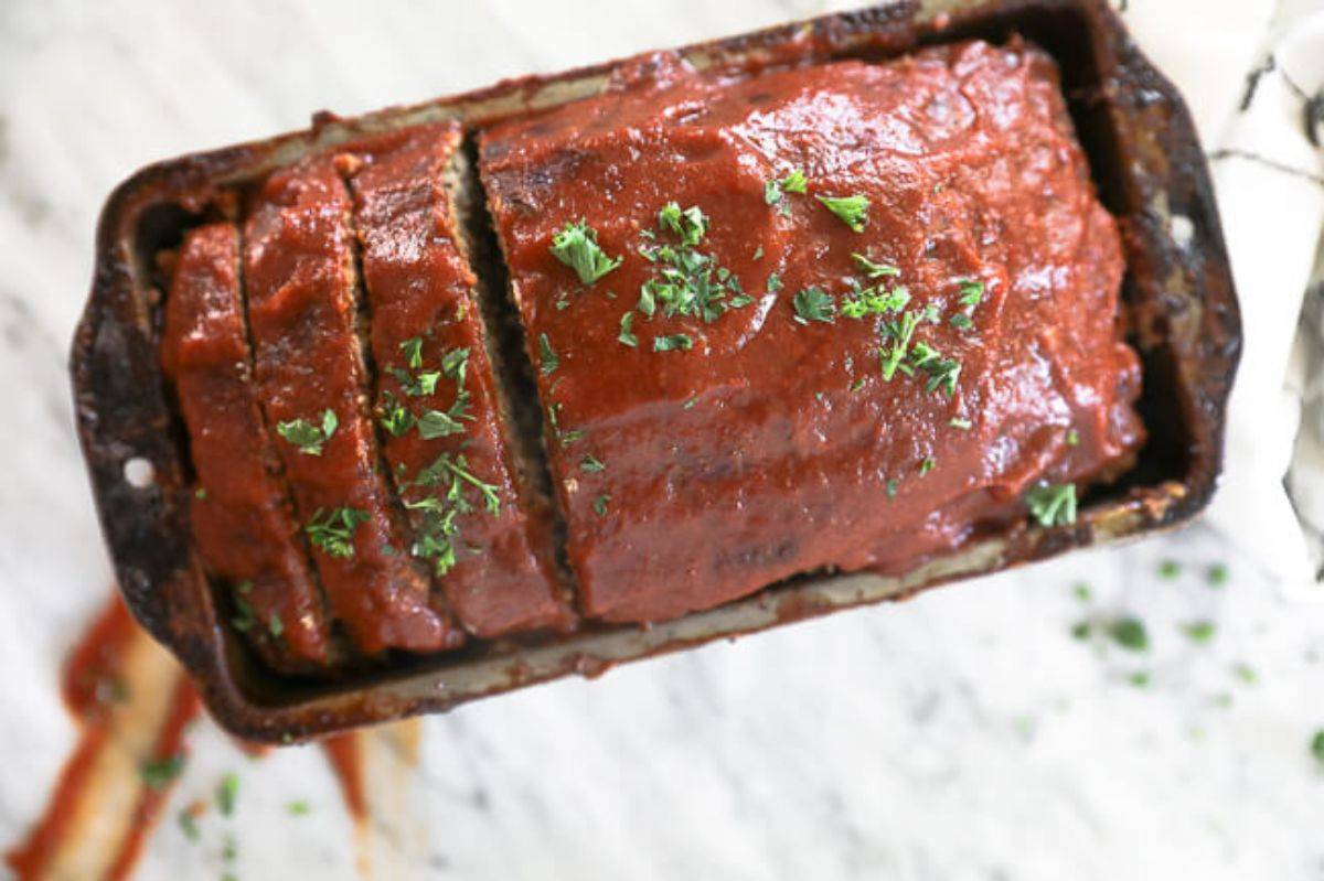 a loaf tin full of meatloaf topped with sauce and chopped herbs