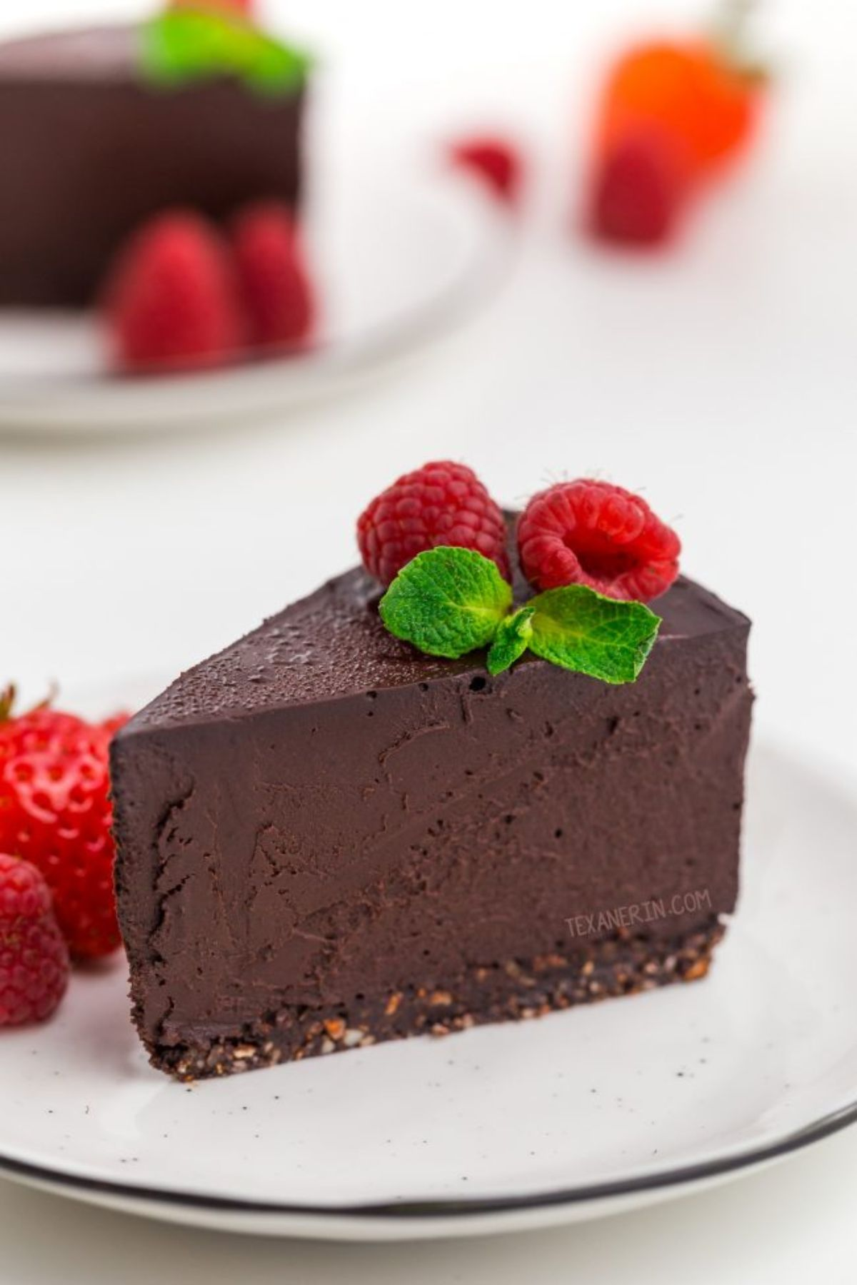 a white plate with a clice of chocolate cheesecake on it, topped with mint leaves and raspberries