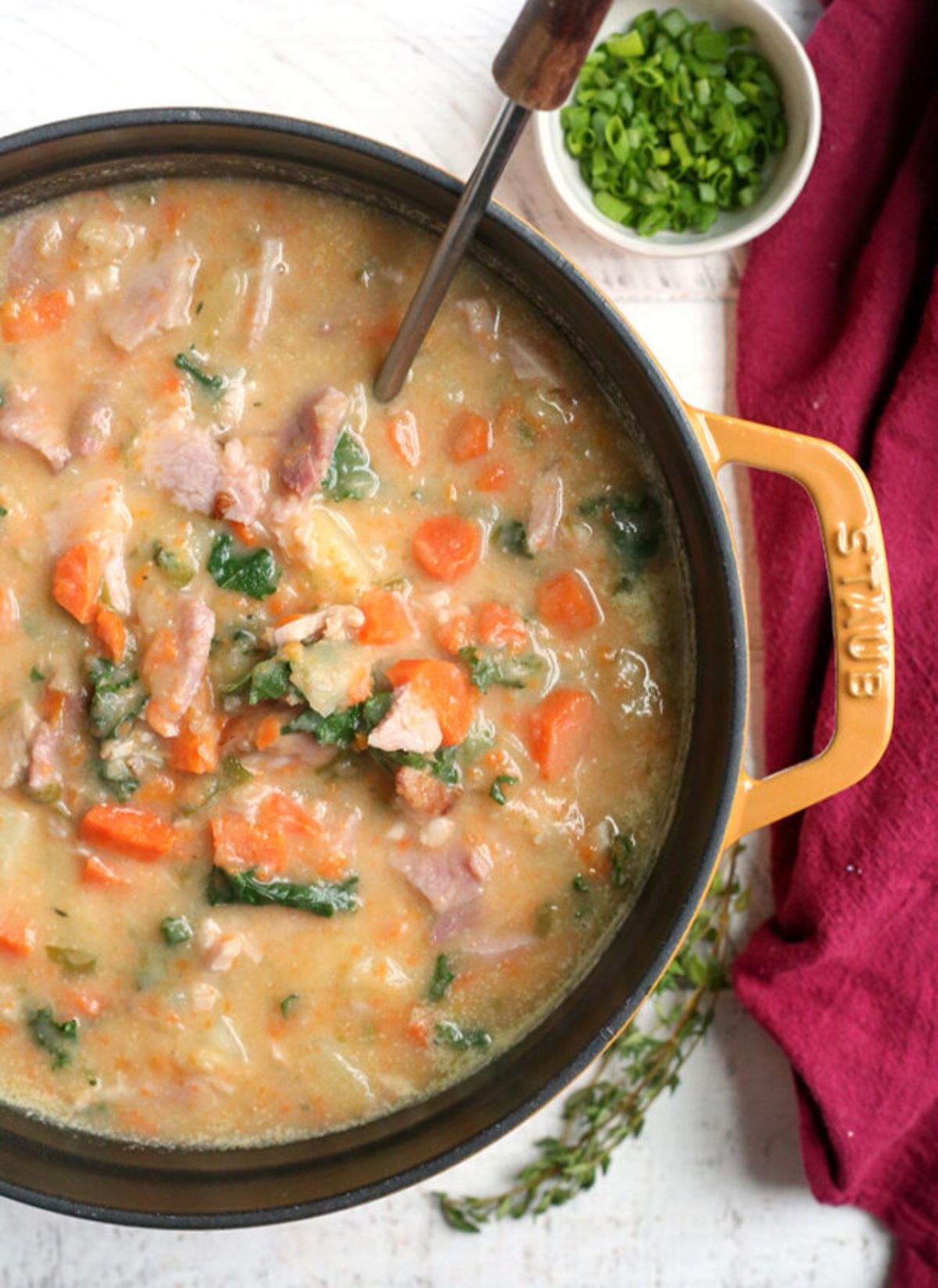 a cast iron casserole dish filled with ham and potato soup with chopped carrots and herbs seen. A spoon is resting in the dish, and a pot of chopped herbs is to the side