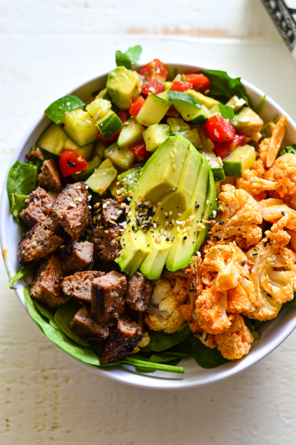 A white bowl of cauliflower, avocado, red meat and chopped salsa